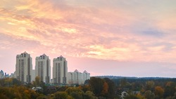 Apartment buildings at sunset. Colorful evening dusky sky high-rise buildings residential area silhouettes over forests background. Evening cityscape of Eastern Europe Belarus city Grodno or Hrodna.