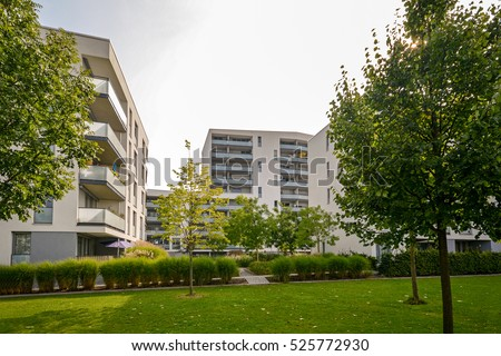 Apartment buildings in the city - Facades of new modern residential houses in green environment