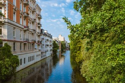 apartment buildings on bank of river or canal in residential district of Hamburg Eppendorf, Germany on sunny summer day