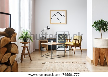 Apartment corner with pictures, end table, plants, wood, and a mustard armchair
