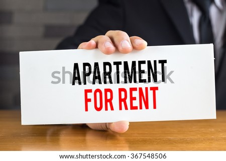 Apartment for rent, message on white card and hold by  businessman