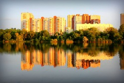 Apartment house on the bank of the lake with forest during sunset.