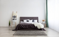 Apartment in simple minimalist Scandinavian design and home interior with furniture. Bed for two with blanket and pillows, stairs, dry plants in vase on gray wall background in modern bedroom, nobody