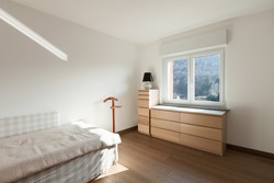 Apartment interior, wooden cupboard under the window of a bedroom