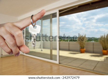Apartment key on the finger of a hand in the interior of an empty apartment.