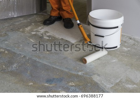 Shutterstock Apartment under construction. Worker puts primer with roller on concrete floor