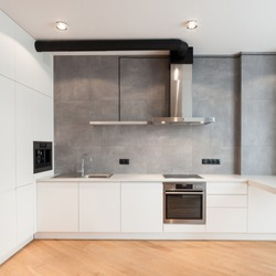 Apartment with contemporary interior. Kitchen in loft style, built in household appliance, electric stove, oven, sink on worktop, wooden laminate on floor and extractor hood on grey wall
