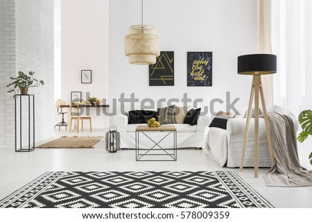 Apartment with white brick wall, sofa, table and pattern rug