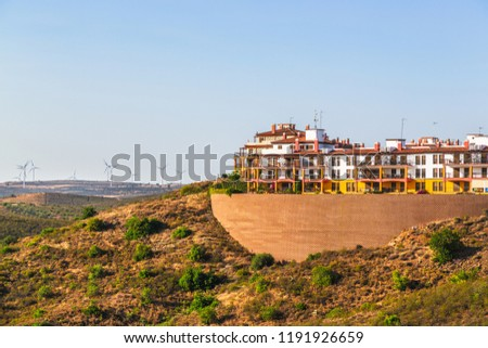 Apartments built high on a hillside in Costa Esuri an urbanisation in Ayamonte, Alongside the River Guadiana in Andalusia, Spain. Turbines in a wind farm can be seen on the hillside
