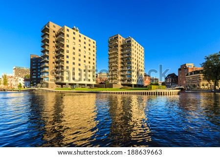 Apartments in a city in evening glow seen from water