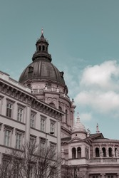 Apex of St. Stephen's Basilica in Budapest, Hungary and details of historical Hungarian downtown buildings on Street Bajcsy-Zsilinszky on a spring day, european architecture, aesthetics pastel colours