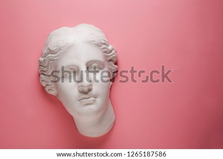 Aphrodite head plaster sculpture on pink background. Beauty and skin care concept, flat lay