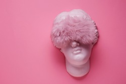 Aphrodite head plaster sculpture with sleep mask on pink background. Beauty and skin care concept, flat lay. Sleeping concept