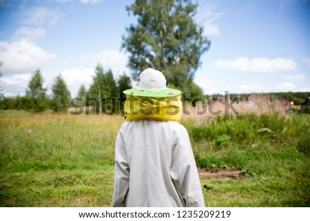 Apiary and beekeeping. A beekeeper in special clothes against bees goes to the hives. Country landscape, agriculture