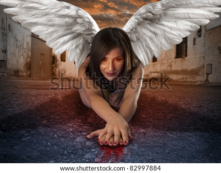 Stock Photo apocalyptic female angel lying in the deserted street with bloody hands under criptic orange sky