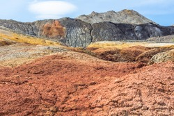 Apocalyptic landscape like a planet Mars surface. Solidified red-brown black Earth surface. Barren, cracked and scorched land. Global warming concept. Refractory clay quarries