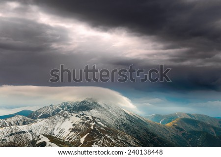 Apocalyptic view on snowy summit of Dumbier peak covered in pillow of clouds in Low Tatras, Slovakia