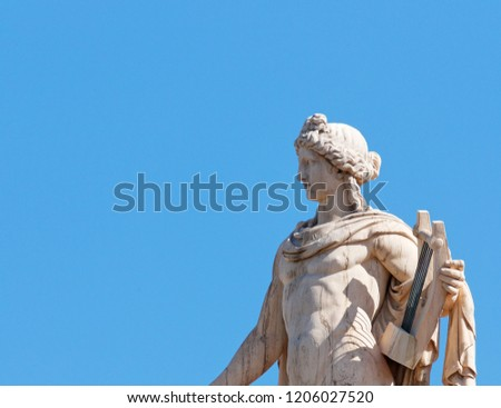 Apollo statue, the ancient greek god of music and poetry, blue sky as space for text #1206027520