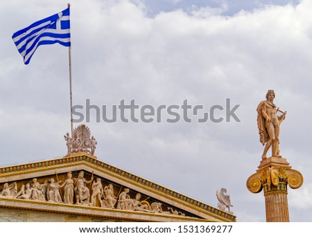 Apollo the ancient Greek god and Greek flag on the Athens academy building