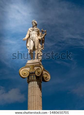 Apollo, the ancient Greek god of arts under impressive sky, Athens Greece