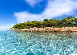 Aponissos beach, a pristine shore at the island of Agkistri, Greece, where turquoise waters meet with the green forest and the clear blue sky.