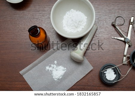 Apothecary can with powder, mortar and pestle, Powder, Apothecary scales on a dark table, top view. Old pharmacy. Manufacturing of medicines.