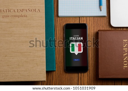 App and textbooks for learning Italian. Books, phone and notepad on student's workplace. Education, foreign languages. #1051031909