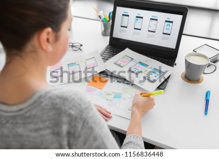app design, technology and business concept - web designer or developer with sketches and laptop computer working on user interface at office #1156836448