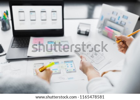 app design, technology and business concept - web designers working on user interface project and drawing sketch in notebook at office #1165478581