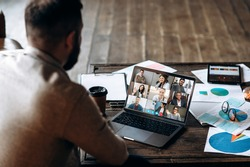 App for communication with employees. Online video conference. Young bearded man communicates via video call with colleagues, he sits at the creative modern office space