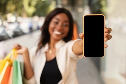 App For Online Store. Happy Black Woman Showing Smartphone With Blank Empty Screen Close Up To Camera And Holding Shopping Bags In Hand, Cheerful Lady Standing Outdoors Mall, Mock Up, Free Copy Space