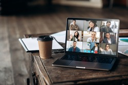App for remote communication. Virtual meeting online. Video conference by laptop. Online business meeting. On the laptop screen, people who gathered in a video conference to work on-line