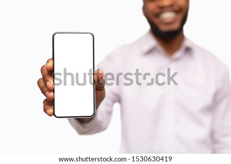 App for your business. Smartphone with blank screen in hands of unrecognizable smiling black man, selective focus on phone, closeup
