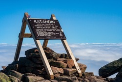 Appalachian Trail northern terminus on Mount Katahdin, in Baxter State Park, Maine.  Wooden sign at the the summit marks the end of the trail.  Summit sits above the clouds.