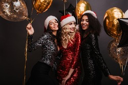 Appealing blonde woman in red dress celebrating winter holidays with friends. Studio shot of girls dancing with balloons.