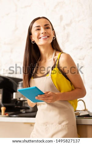 Appealing businesswoman. Appealing businesswoman owning coffee shop holding little blue tablet #1495827137