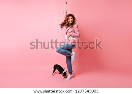 Appealing girl dancing beside black french bulldog. Blissful ginger lady jumping on pink backround during photoshoot with dog.