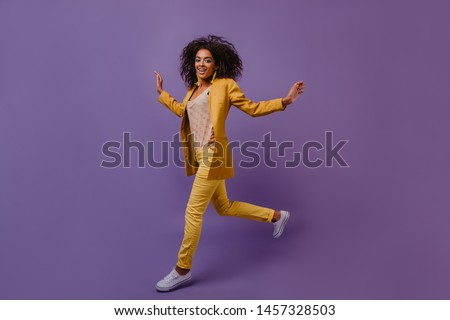 Appealing girl with wavy hair jumping in studio. Attractive african woman wears yellow costume dancing during photoshoot.