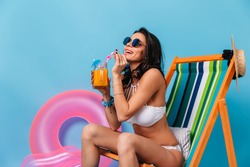 Appealing tanned girl sitting on deck chair and drinking cocktail. Studio shot of lady in sunglasses posing on chaise longue on blue background.