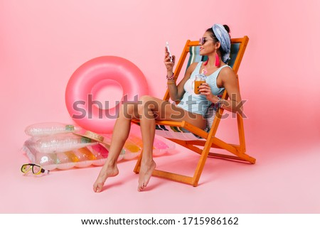 Appealing woman in swimsuit sitting in deck chair. Amazing young lady with glass of juice chilling on pink background.