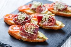 Appetizer bruschetta with prosciutto, tomato, zucchini on ciabatta bread on stone slate background close up. Delicious snacks, sandwiches, crostini, antipasti on party or picnic time. Top view