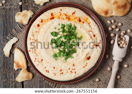 Appetizer creamy hummus tasty traditional food with tahini paste, olive oil, paprika and parsley in rustic plate on vintage wooden background