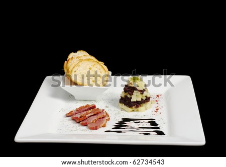 Appetizer: Duck meat, blood sausage, apples and baguette on white plate isolated on black (Focus on apple and blood sausage pile)