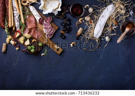 Appetizer, italian antipasto, Ham, Olives, Cheese, Grissini bread sticks,  Sausage on dark blue background copy space. Top view, copy space.