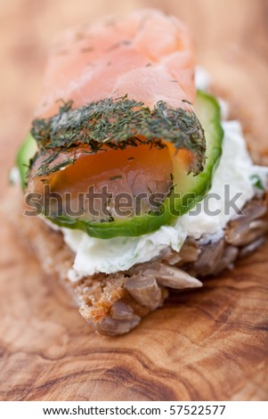 Appetizer of smoked salmon, cucumber and cream cheese on a slice of brown bread. Shallow DOF