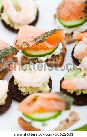 Appetizer of smoked salmon, prawns, cucumber and cream cheese on a slice of brown bread. Shallow DOF