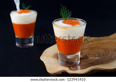appetizer of sweet pepper, cream and red caviar in a glass goblet on a wooden board on a black background