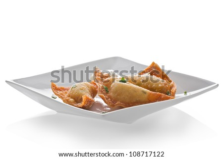 Appetizer plate with three pieces of crab rangoon and a mustard sauce against a white background.