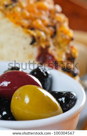 Appetizer platter with bread, cheese, meat, olives, and oil and vinegar.