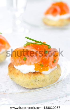 appetizer - potato bun with salted salmon, red caviar and green onion on a glass plate closeup vertical